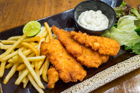Healthy fish and chips in a black dish on wood table background for ready to serve.