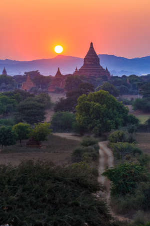 View from afar of the ancient pagodas (stupas) visible among rugged fields and trees of other pagodas and mountains on the horizon during sunset or sunrise, in Bagan, Myanmar (Burma)