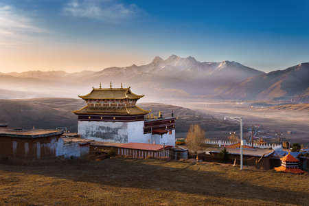 Chinese temple or tibet style with Landscape View snow of Mountain in the winter season and landmarks public place in Long Youth Cole temple Ganzi, Sichuan, China at morning twilight