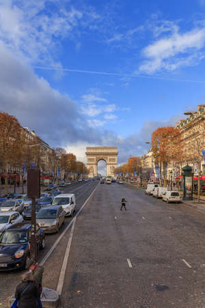 PARIS, FRANCE - DECEMBER 11, 2014: Traffic in front of The Arc de Triomphe de lEtoile is one of the most famous monuments, View of the Champs-Elysees Avenue is full of stores, cafes and restaurants.