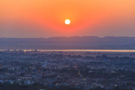 Beautiful sunset in Mandalay, Myanmar (Burma) with lake mountains, temples and pagodas seen from mandalay hill.