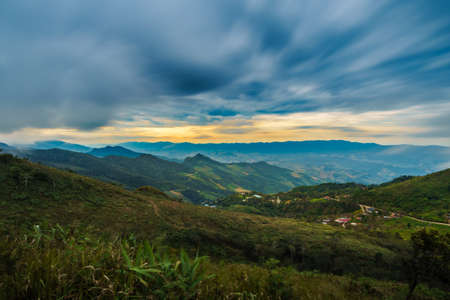 Green field on the mountain with cloud, blue sky & yellow light sky, Chiang Rai hills village landscape panorama. Northern Thailand