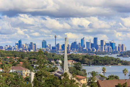 A view of Watsons Bay and the distant skycrapers of Sydney CBD, Water with Yacht, Harbour Bridge and Cityscape in background Stock Photo