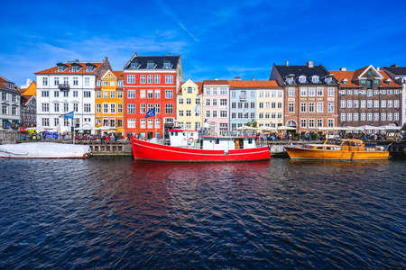 Boats before colourful houses on Nyhavn canal in Copenhagen