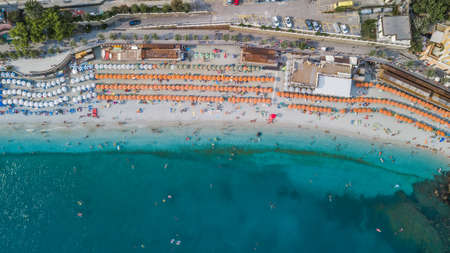 Aerial drone shot view of Monterosso beach filled with parasol in summer time