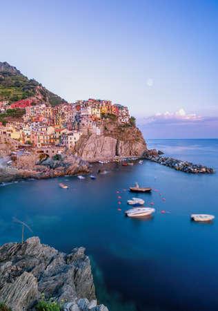 Disparo de larga exposición de Manarola con Rock en primer plano en Cinque Terre, Italia durante las horas del atardecer
