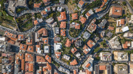 Overhead aerial view of red orange houses and trees in La Spezia in Italy