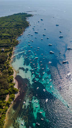 aerial drone shot view of coast line of Ile Sainte Marguerite and yachts in mediterranean sea, south France