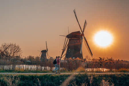 Tourists passing by wind mill in Kinderdijk during sunset near Rotterdam