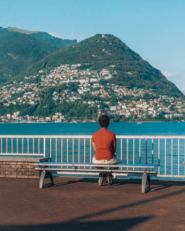 Tourist gaze at Monte Bre by Lake Lugano in summer time afternoon