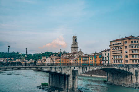 Ponte Garibaldi bridge voer Adige river with Verona Church in the background in Verona, Italy