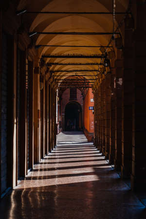 Portico passage with roman style columns with morning sunlight in Bologna, Italy