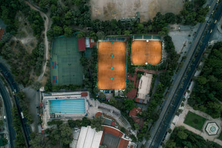 Aerial overhead drone shot of tennis court with lights and swimming pool at dusk in Athens