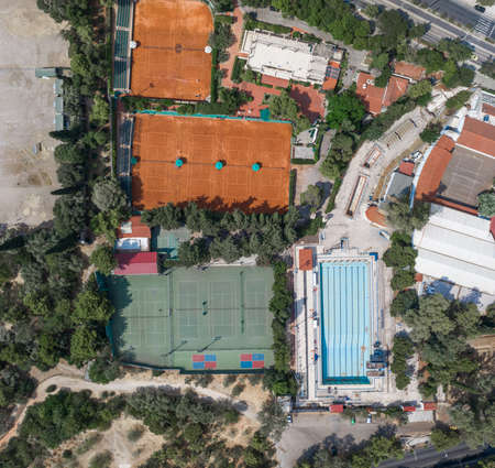 Aerial overhead drone shot of hard and clay tennis court besides swimming pool in Athens
