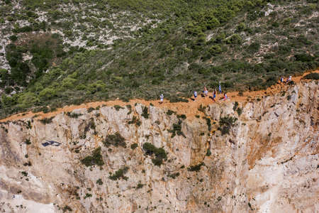 Zakynthos, Greece - August 20, 2019: Aerial drone shot of tourists on dangerours cliff to see shipwreck bay navagio beach Editorial
