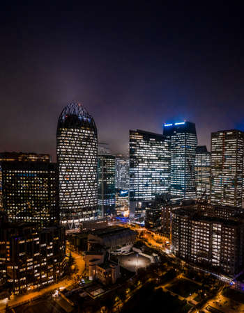 Aerial drone night shot of Skyscrapers with lights on in La Defense, financial district of Paris