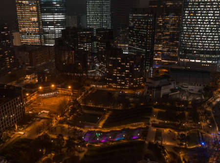 Aerial drone night shot of Parc Diderot with color lighted fountain with La Defense Skyscrapers in background