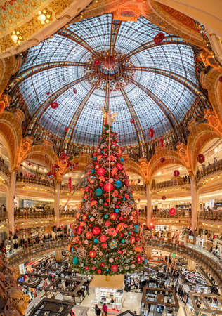 Paris, France - December 15: Massive Christmas tree decoration with flowers inside Galerie Layfayette shopping mall Éditoriale