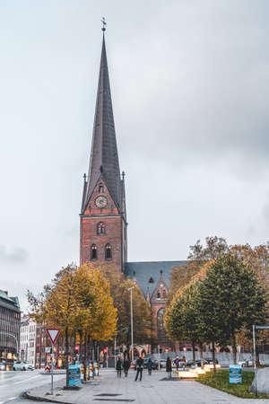 Hamburg, Germany - November 9, 2019: People walk on the street towards thurch of Petrikirche after sunset