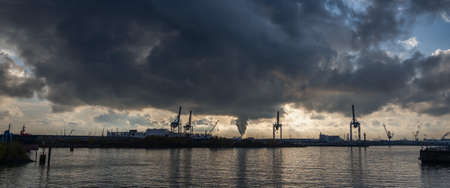 Panoramic view of Hamburg Harbor from Hansestadt with dramatic stormy clouds and sunlight