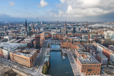 Aerial drone view of port of Hamburg before sunset with clouds aover historical city center