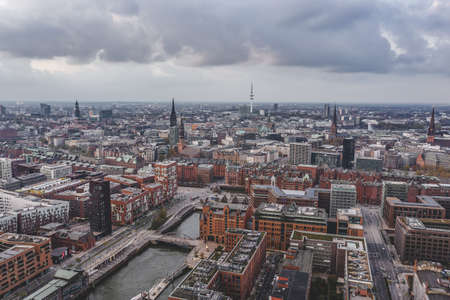 Aerial drone view of Port of Hamburg with clouds over historical city center and sea port