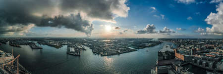 Aerial drone panoramic view of port of Hamburg from Hafencity before sunset with dramatic stormy clouds and sunlight over the horizon Stock Photo