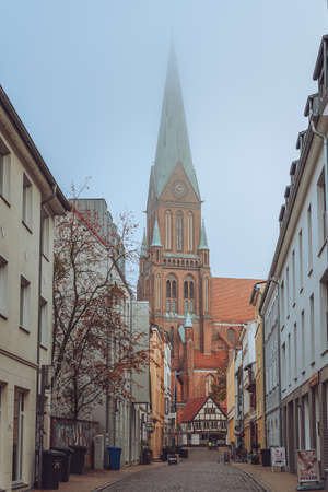 Schwerin, Germany - Novermber 11, 2019: Street view of clock tower of Schwerin Cathedral with fog