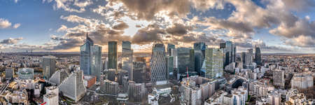 Paris, France - December 09, 2019: Aerial panoramic drone shot of La Defense skycraper with park diderot in Paris with clouds before sunset