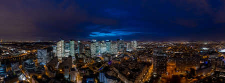 Aerial pano drone shot of La Defense CBD buildings complex after sunset with lights on