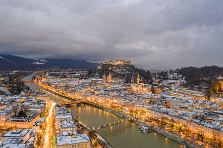 Panoramic aerial drone shot view of snowy Salzburg by river after sunset with heavy clouds after storm rain in winter