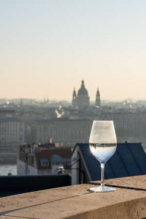Refelction of St. Stephen basilica in wine glasses and vague silhouette in the background in winter