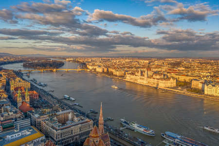 Aerial drone sunset view of Hungarian Parliament by Danube river during golden hour in winter budapest