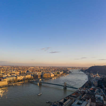 Aerial drone view of Danube river with bridges in Budapest during sunset hour in winter