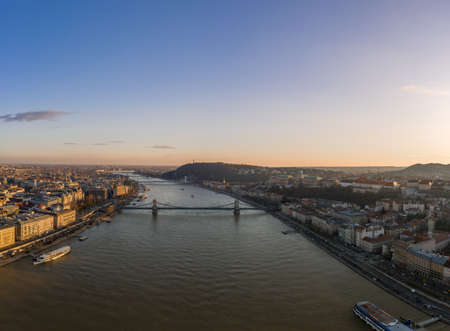 Aerial drone shot of Danube river with chain bridge and Buda Castle in Budapest in Sunset hour in winter