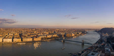 Aerial panoramic drone view of Danube river with bridges in Budapest during sunset hour in winter