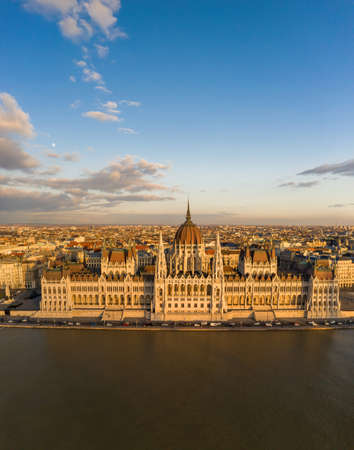 Aerial drone view of Hungarian Parliament facade by danube river in Budapest sunset hour in winter