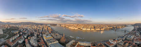 Wide panorama aerial drone view of Parliament by danube river in Budapest sunset hour in winter