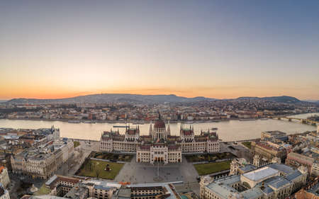 Aerial drone shot of Hungarian Parliament by Danube river in Kossuth Square in Budapest sunset in winter