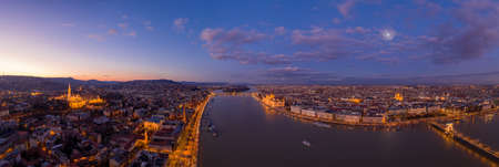 Panoramic aerial drone shot of Danube river with lighted quai with purple sky during Budapest sunset. High quality photo