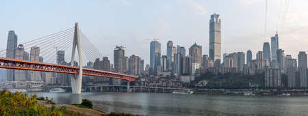 Qian si men suspension bridge over Jialing river, after sunset, view from river bank in Chongqing, southwest China