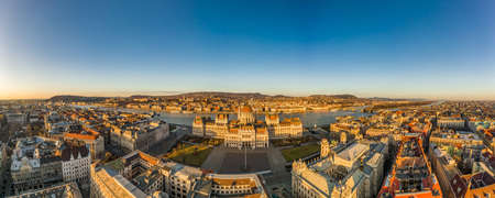 Panoramic Aerial drone shot of east side facade of Hungarian Parliament Kossuth Square during Budapest sunrise