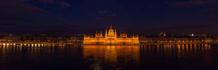 Panoramic aerial drone shot of Hungarian Parliament with lights on during Budapest evening Stockfoto - 151029364