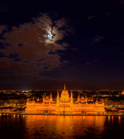 Aerial drone shot of Hungarian Parliament with lights on during Budapest evening