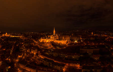 Aerial drone shot of Matthias Church with lights on Buda Hill in Budapest evening Stockfoto - 151029515