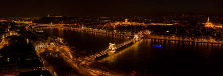 Panoramic aerial drone shot of Chain bridge over Danube and National Gallery with lights in Budapest night