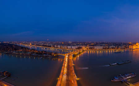 Aerial drone shot of Margaret Bridge with lights on over Danube river during Budapest sunset Stockfoto - 151134189