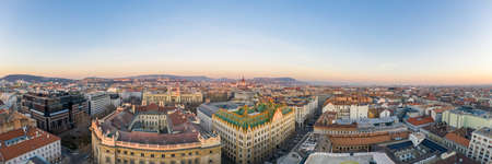 Panoramic Aerial drone shot of art nouveau rooftop postal bank in Budapest dawn with Parliament view Stockfoto - 151134229