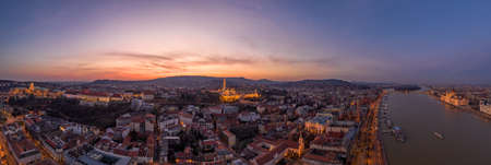 Panoramic aerial drone shot of lighted Matthias Church Buda castle on Buda Hill by Danube in Budapest sunset