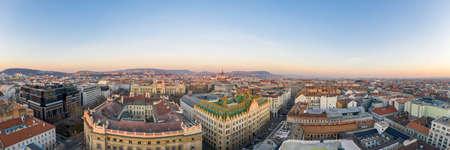 Panoramic Aerial drone shot of art nouveau rooftop postal bank in Budapest dawn with Parliament view Stockfoto - 151134252